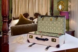 The Globe-Trotter Goring Hotel Edition_open wiht dress on bed_landscape_hi res